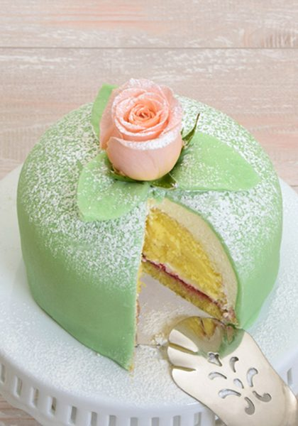 Traditional Swedish princess cake or prinsesstårta made with vanilla sponge cake, creme, raspberry jam and covered with green marzipan.